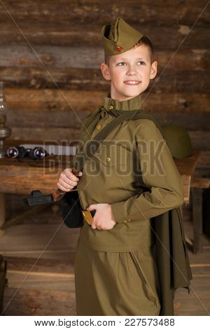 Russian boy in the old-fashioned Soviet military uniform on the background of a dugout from the bars