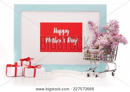 Shopping trolley with brenches of Lilac, pearl beads, gift boxes and frame with blank space on white background. Copy space for adding your content.  Advertising. Greeting card. Mothers day.