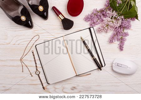 Trendy woman's desk with blank notepad for text, computer mouse, gifts, jewelry,cosmetics and lilac flowers on ligth wooden background. Top view. Mockup.