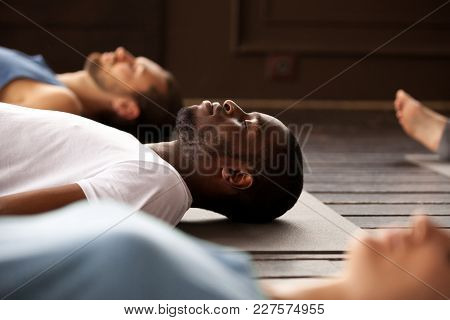 Group Of Young Afro American And Caucasian Sporty People Practicing Yoga Lesson Lying In Dead Body O