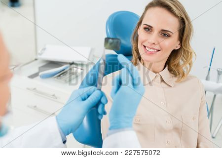 Dentist Showing Female Patient X-ray In Modern Dental Clinic