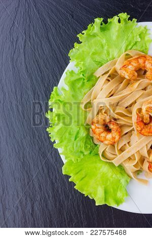 Dish With Pasta And Shrimp On The Surface Of Slate. Tagliatelle Macaroni Are Observed With Fried Lan