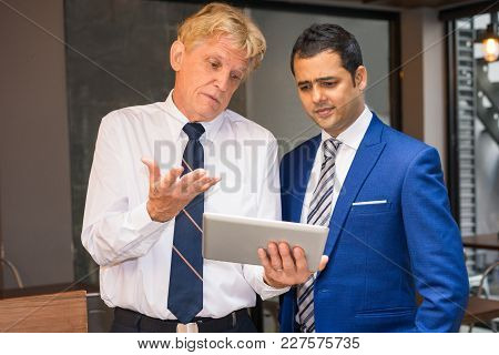 Two Puzzled Men In Ties Looking At Tablet Screen. Managers Having Video Chat With Boss And Explainin