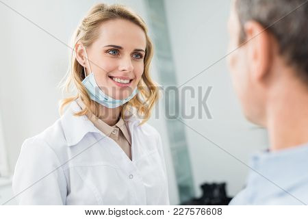 Smiling Doctor Listening To Patient In Modern Dental Clinic