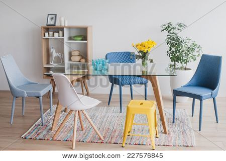 Pastel Chairs On Glass Table In Dining Room
