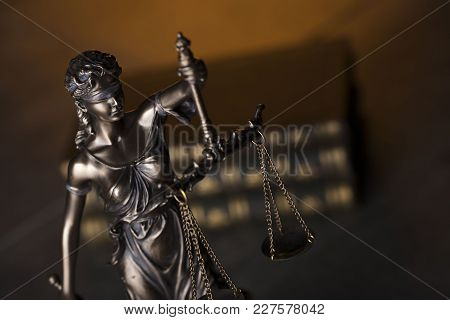 Law and justice concept. Themis statue and books on brown background.