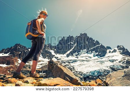 Woman hiker stands on the rocky ground with mountain and glacier on the background. Cerro Castillo mountain, Chile