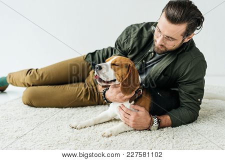 Handsome Man Lying On Carpet With Cute Beagle