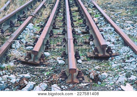Abandoned Rusty Rails. Steel Rails At Old Closed Railway Station.  Metal Material Is Waiting For Tra