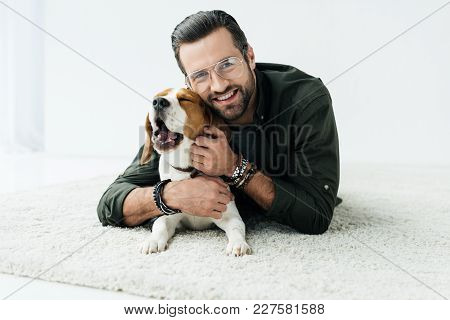 Smiling Handsome Man Lying On Carpet With Cute Beagle And Looking At Camera