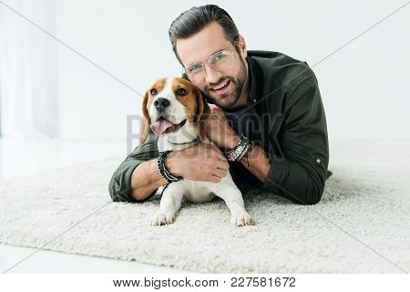 Happy Handsome Man Lying On Carpet With Dog And Looking At Camera