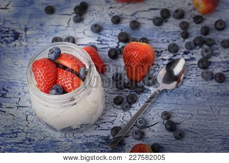 Yogurt In A Jar, With Strawberries And Blueberries. Natural Milk Dessert Close-up With Vignette. Use