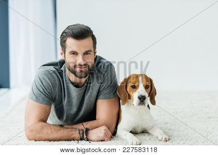 Handsome Man Lying With Cute Beagle On Carpet And Looking At Camera