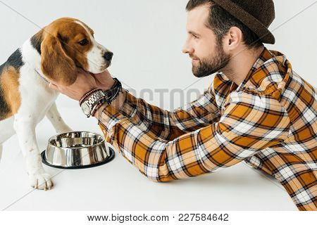 Side View Of Man Palming Dog At Table With Pet Bowl
