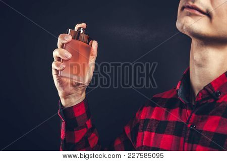 Young Man Applying Perfume On His Neck On Black Background