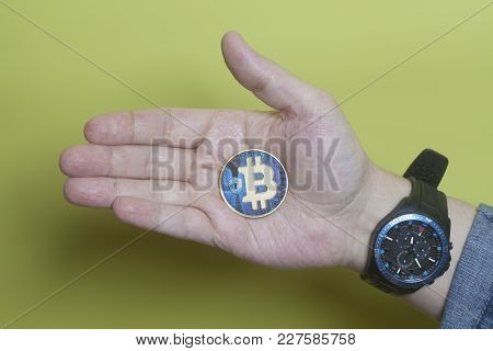 Virtual Coin Blue Bitcoin Holding Hand On Yellow.