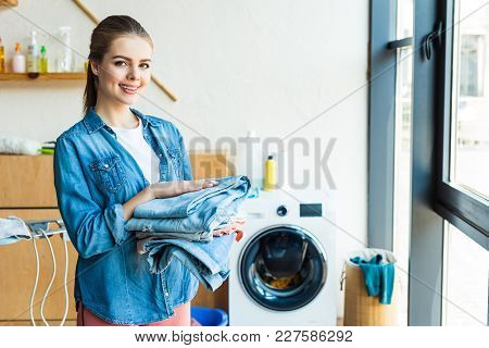 Young Woman Holding Clothes And Smiling At Camera While Standing Near Washing Machine At Home