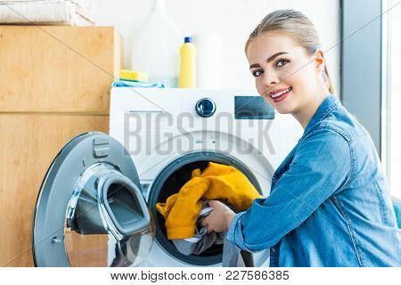 Young Woman Smiling At Camera While Putting Laundry Into Washing Machine