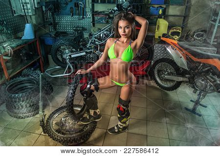 Sexy Girl In Garage With Motorcycles Posing With Studded Tires
