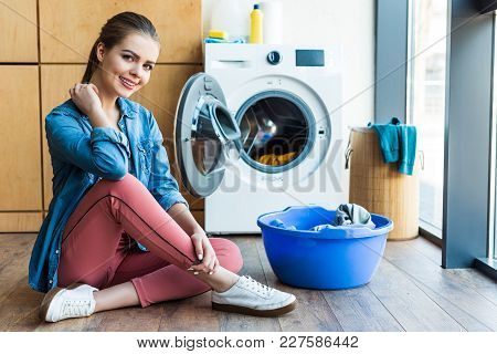 Beautiful Young Woman Smiling At Camera While Sitting Near Washing Machine And Plastic Basin With La