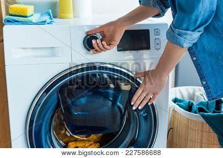 Cropped Shot Of Woman Using Washing Machine At Home