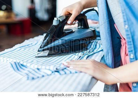 Close-up Partial View Of Young Woman Ironing Clothes At Home
