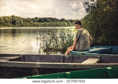 Teenager Boy Lonely Contemplation Countryside Landscape On River Bank During Countryside Summer Holi