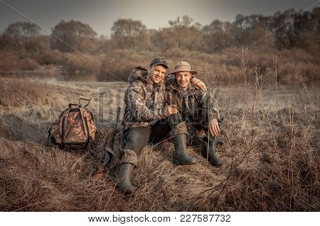Hunter Men Friends Resting Recreation  In Rural Field During Hunting Period Symbolizing Strong Frien