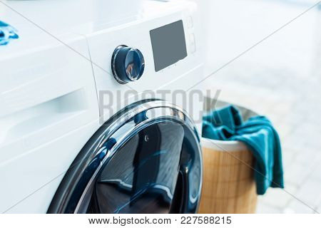 Close-up View Of Modern Washing Machine And Basket With Laundry At Home