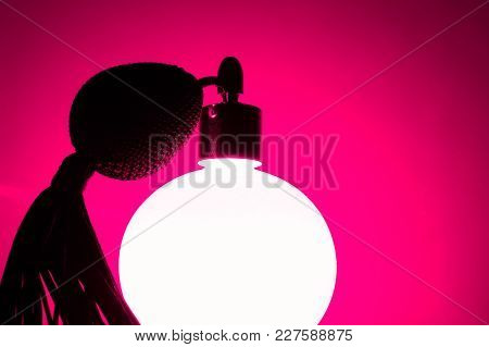 Glowing Vintage Pink Perfume Bottle In Deep Pink Background. Very Sexy And Passionable Atmosphere