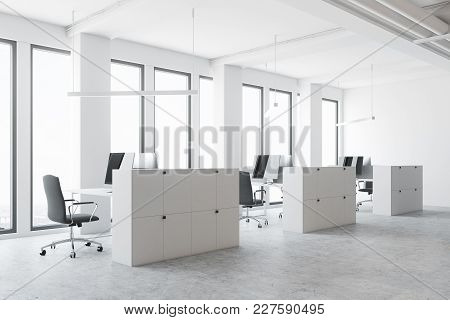White Open Space Office Corner With A Concrete Floor, Large Windows, And White Cubicles With Compute