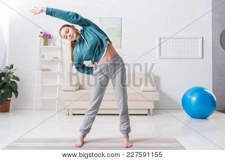 Girl Stretching Body On Yoga Mat At Home