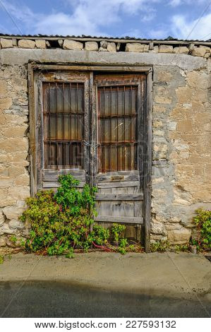 Old Wooden Doors With Rusted Rectangular Bars On The Top Section, Chained Closed With A Plant Growin