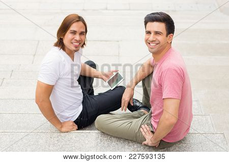 Closeup Portrait Of Two Smiling Handsome Young Men Turning Round To Camera, Holding Tablet Computer