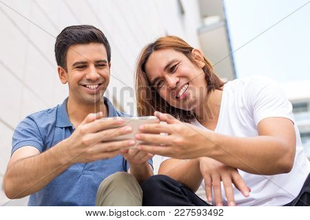Closeup Portrait Of Two Smiling Handsome Young Men Using Smartphone Outdoors And Sitting. Technology