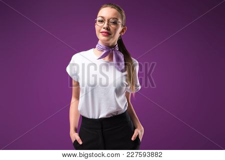 Smiling Girl With Hands In Pockets Looking At Camera Isolated On Purple