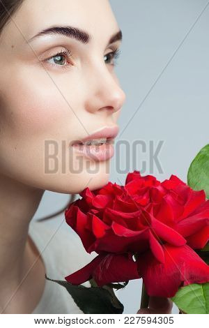 Beauty Fashion Model Woman Face. Portrait With Red Rose Flowers.
