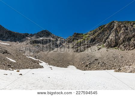 Snow field and rock faces in an alpine surrounding at the Gamswanne (Gams Valley) at Grosser Wilder Mountain (Big Wild). Oberstdorf, Germany
