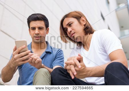 Closeup Portrait Of Two Serious Handsome Young Men Browsing On Smartphone And Sitting. Technology Co