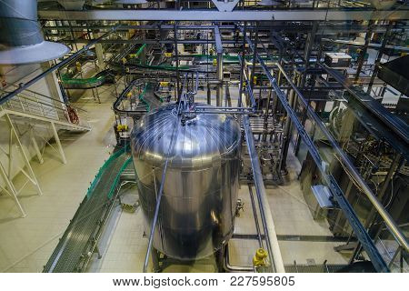 Modern Brewery Production Line. Large Vat For Beer  Fermentation And Maturation And Conveyor Belts.