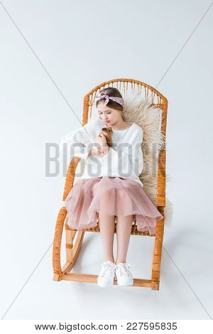 Beautiful Girl Holding Furry Rabbit While Sitting On Rocking Chair Isolated On White