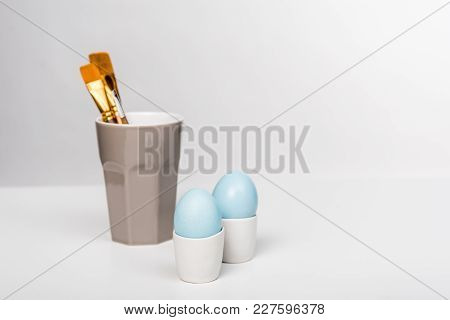 Close-up View Of Blue Painted Easter Eggs And Paint Brushes In Cup On Grey