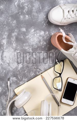 Summer Holiday , Travel, Study Or Sport Concept: Smartphone , White Sneakers, Notepad, Headphones An