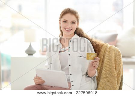 Young woman shopping online with credit card and tablet at home