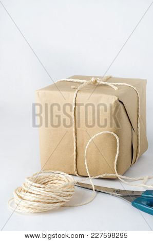 A Brown Paper Parcel Tied To A Knot With String. Remnants Of String Ball In Foreground With Closed P