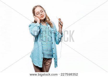 Cute Teenage Girl In Eyeglasses Listening Music With Smartphone Isolated On White