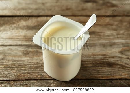 Plastic cup with yummy vanilla yogurt on wooden table poster