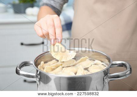 Woman cooking dumplings in boiling water, closeup