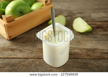 Plastic cup with yummy apple yogurt on wooden table