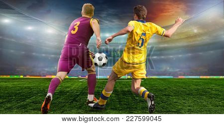 Soccer ball on the field of stadium with light .  Footballer goes to the Takaku at the opponent's gate .